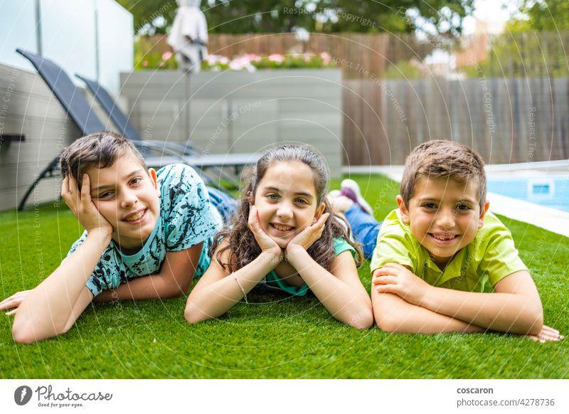 Portrait of three kids lying on a grass background beautiful boy casual caucasian cheerful child childhood children enjoy family field friends friendship fun