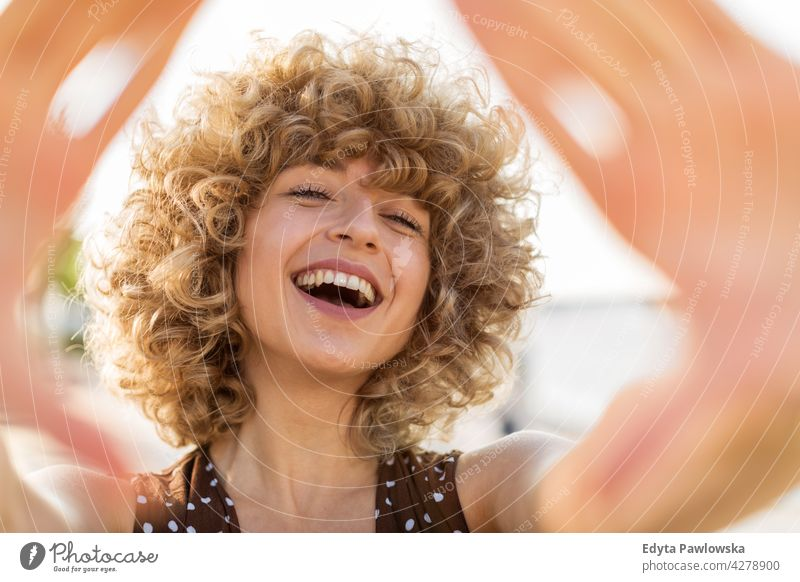 Portrait of young woman with curly hair smiling millennials urban street city stylish people young adult casual attractive female happy Caucasian toothy