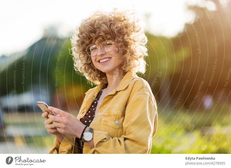 Young woman with mobile phone in the city millennials urban street stylish people young adult casual attractive female smiling happy Caucasian toothy enjoying