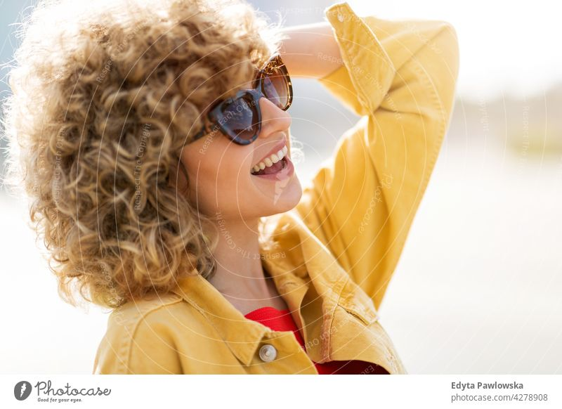 Portrait of young woman in sunglasses millennials urban street city stylish people young adult casual attractive female smiling happy Caucasian toothy enjoying