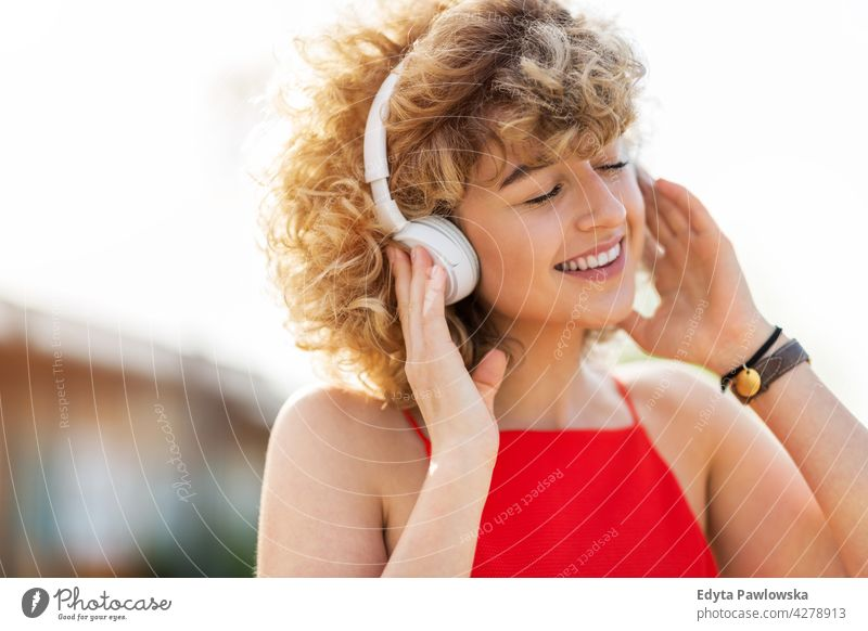 Portrait of young woman wearing headphone millennials urban street city stylish people young adult casual attractive female smiling happy Caucasian toothy