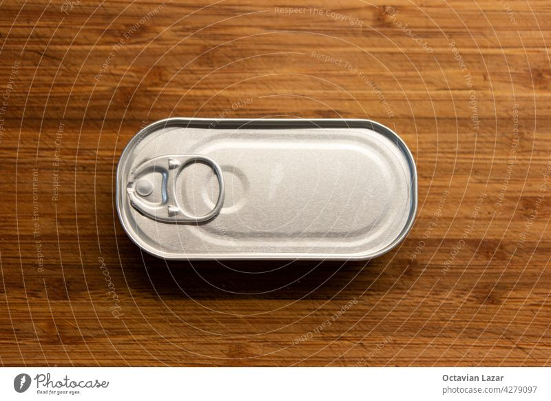Unopened fish tin can on a wooden kitchen board top view no brand or writing blank above tincan aluminium opener cooking pull goods closed nobody recycle