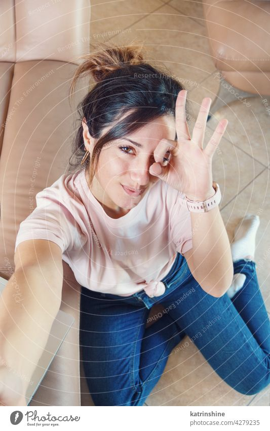 Young women sitting on the floor and taking selfie while showing OK finger sign ok gestures signm smile wear mockup t-shirt top view hand Lifestyle jeans indoor