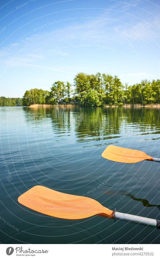 Kayak paddles rest over the water, selective focus. kayak sport nature canoe nobody activity vacation oar adventure equipment leisure journey holiday lifestyle