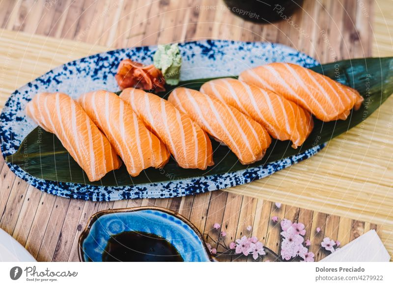 Plate of salmon niguiri with soy sauce in a sushi restaurant appetizer asia asian assorted background closeup closeup japanese food cuisine culture delicacy