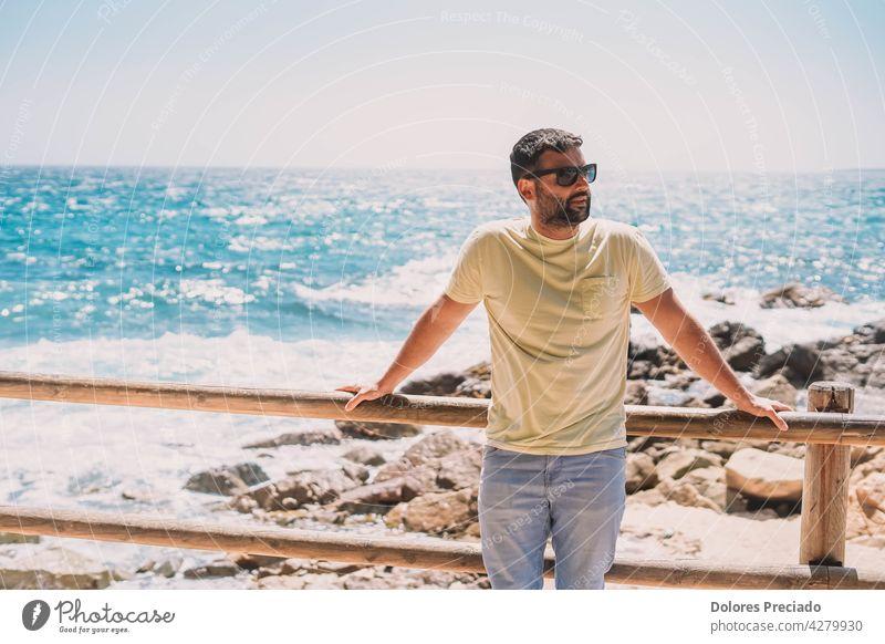 man enjoying a sunny day on the coast adult attractive beach beard blue boats boy brunet caucasian cute enjoyment face fun guy handsome happy lifestyle looking