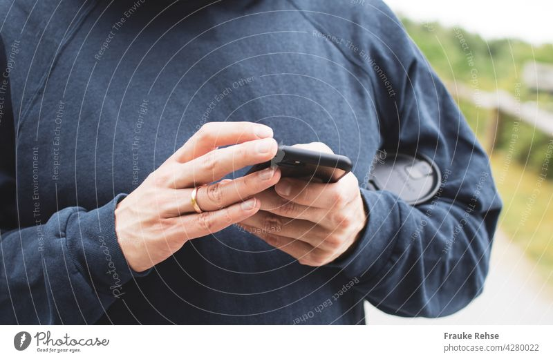 Close-up of a man with a coffee mug under his arm, busy with a black smartphone mobile work hands Cellphone Technology Telephone Internet Hand using Lifestyle