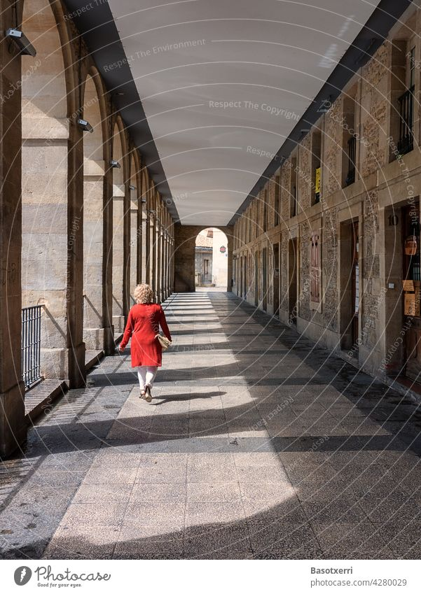 Woman in red coat crosses arcade in old town. Los Arquillos, Vitoria-Gasteiz, Basque Country, Spain Vitoria Gasteiz Arcade passage Red Arch Corridor archway