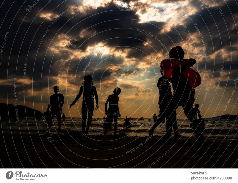 Silhouettes of people playing in the sea at a public beach silhouette landscape sky sand evening vacation sun sunset together summer young ocean water nature