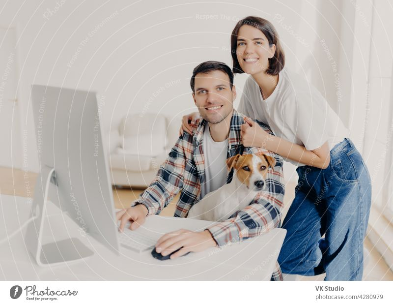 Image of happy brunette smiling woman leans at husbands shoulders who keyboards on computer, surf internet and search new apartment to buy on website, pose in spacious room with domestic dog