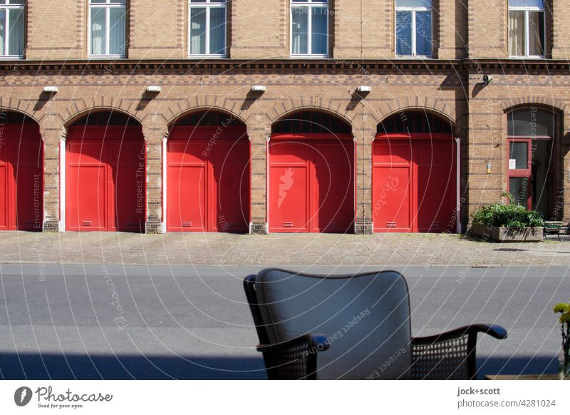 Seat in front of the fire station Firehouse Chair back Brick facade Arch Garage door Highway ramp (exit) Sidewalk Symmetry Architecture Highway ramp (entrance)
