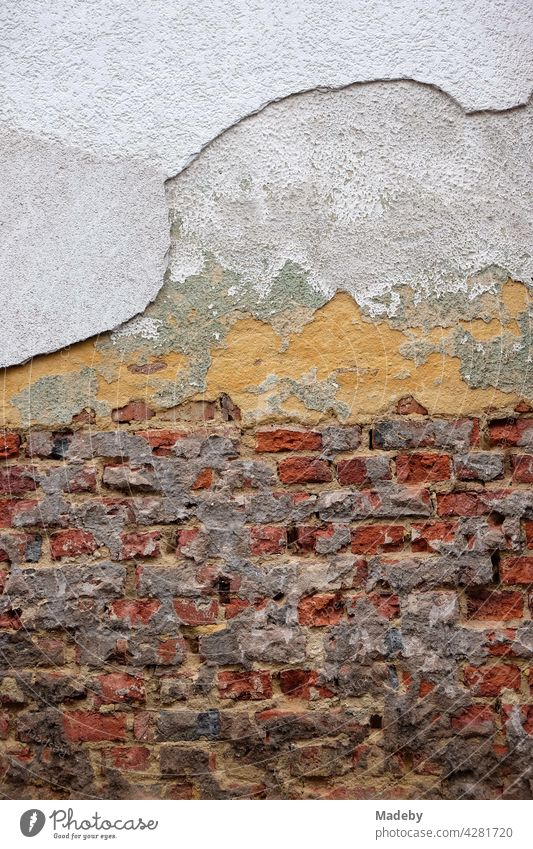Crumbling plaster and exposed old masonry of red brick of an old building in Wettenberg Krofdorf-Gleiberg near Giessen in Hesse Wall (building) Facade