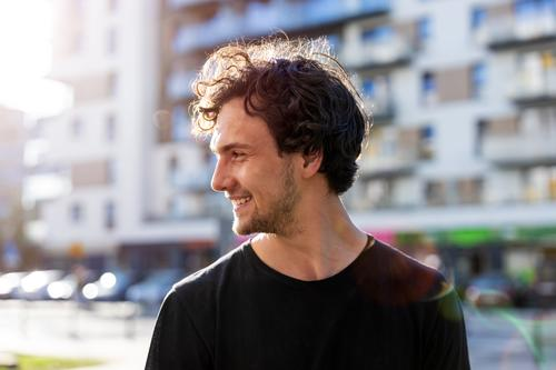 Portrait of a handsome young man in the city sunny outside curly hair hipster person adult confidence outdoors summer male attractive natural one portrait
