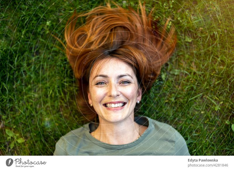 Carefree woman lying on the grass in the sun high angle daydreaming above rest green lawn meadow park nature spring red hair redhead sunny outside pretty girl