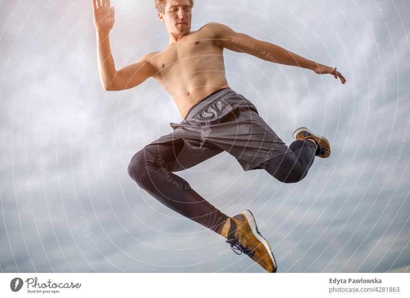 Man jumping against the sky people person guy fashionable serious sexy fit slim body hair style standing one stylish caucasian man boy expression men lifestyle