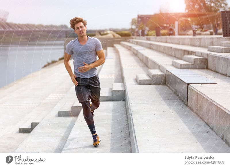 Young man running in urban area Jogger runner jogging people young male energy exercise clothing exercising fitness recreation sport healthy lifestyle action