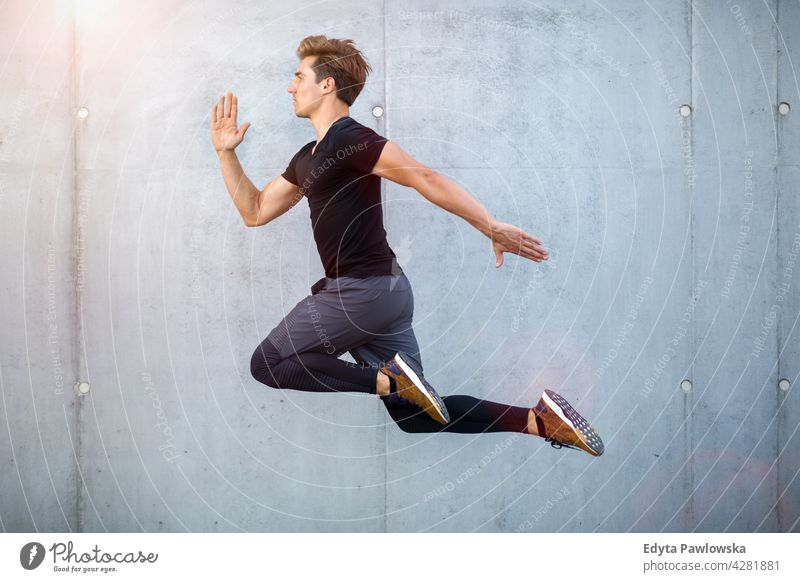Handsome young man jumping against grey wall people person guy fashionable serious sexy fit slim body hair style standing one stylish caucasian boy expression