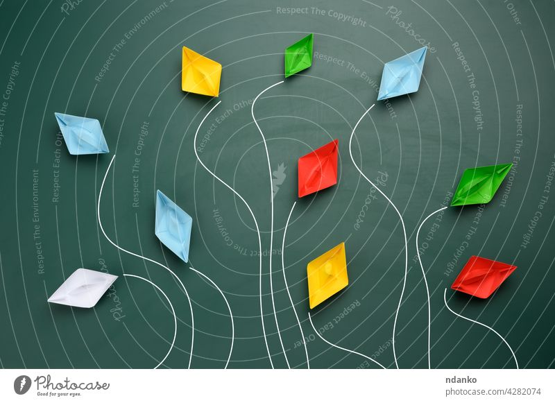 a group of multi-colored paper boats flies in different directions on a green background blue boss business competition concept creative creativity dispute