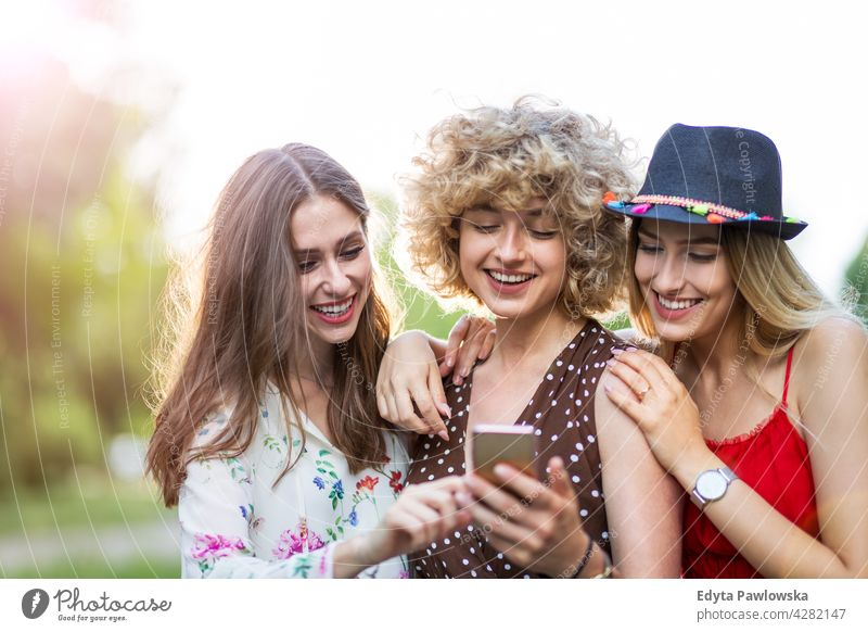 Happy young women having fun with smart phone sunset summer group together people woman casual beautiful attractive girl girls female three people friends