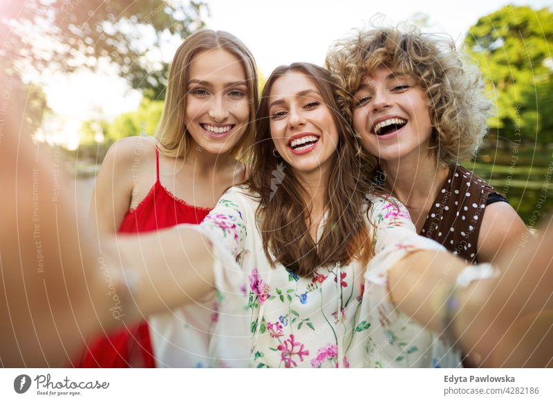 Three friends taking selfies sunset summer group together people woman women young casual beautiful attractive girl girls female three people friendship smiling