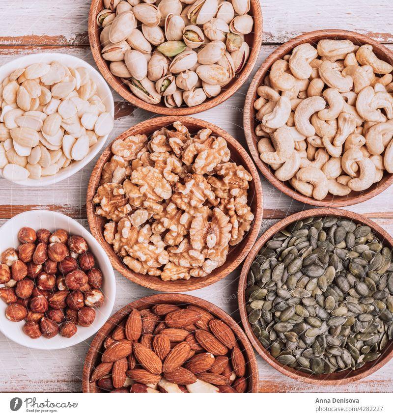 Different kind of nuts in wooden bowls assortment walnut selection snack hazelnut mix healthy seed pistachio pumpkin seeds cashew almond brazilian nut hazelnuts
