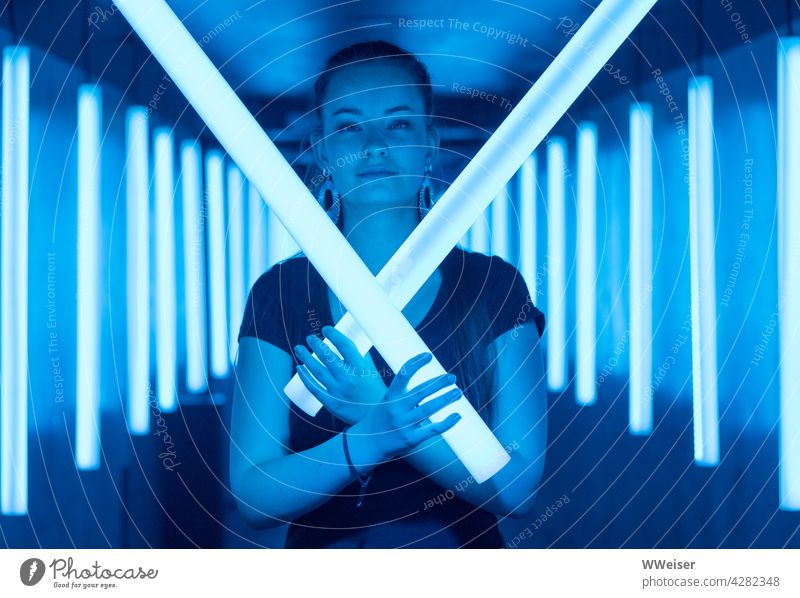 A beautiful young woman knows how to defend herself: May the Force be with her! Light Light tubes Woman Girl Face pretty Young woman Lightsabers Blue