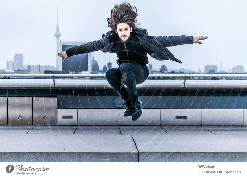 Dynamic young man with long hair lands on the roof of a big city Man Jump energetic youthful Spirited Roof Above Reichstag Parkour panorama courageous masculine