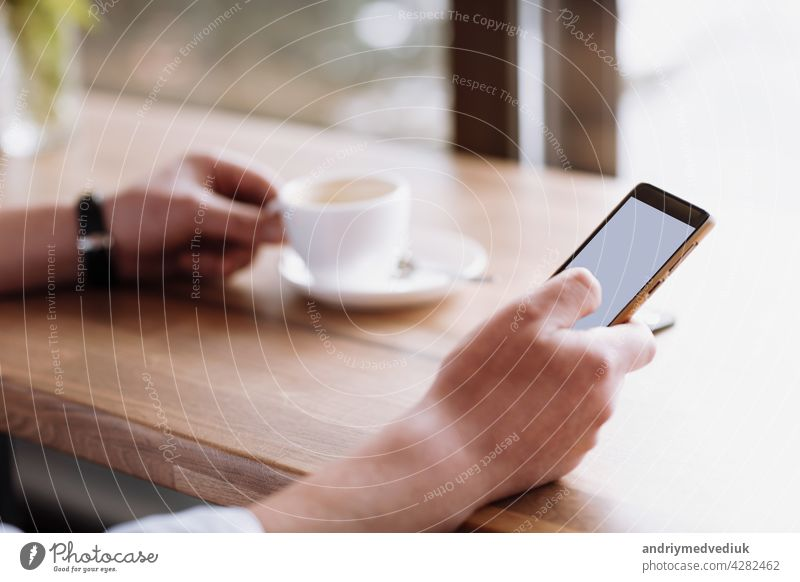businessman hand holding a phone with isolated screen against moke up and drink coffee in the coffee shop blurred coffee cup background, Mock up concept