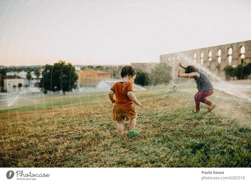 Brother and sister playing with water sprinklers Brothers and sisters Child Water Summer Refreshment Exterior shot Playing Human being Joy Colour photo Infancy