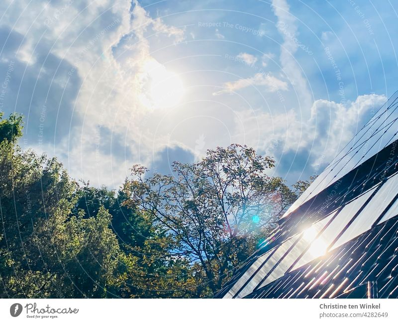 The sun shines brightly from the slightly cloudy sky and is reflected in the collectors of the solar system and the photovoltaic system of a residential house.