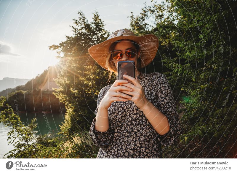 woman with hat and sunglasses using mobile phone in sunset on the lake side 5g adult app attractive background beautiful beauty caucasian communication