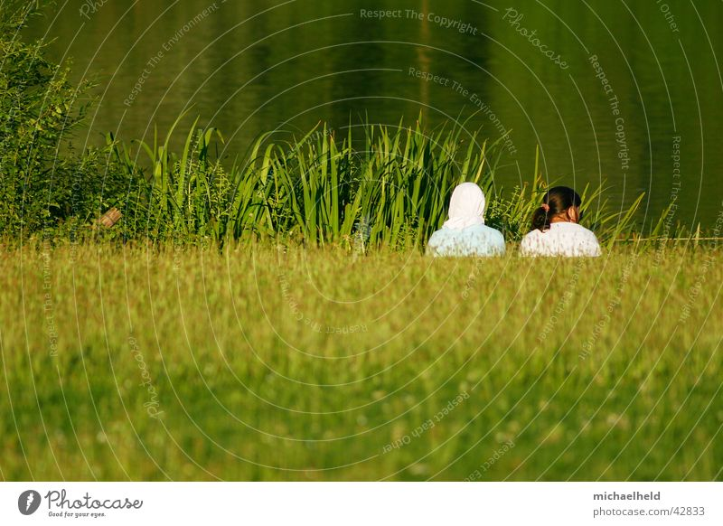 Two alone 2 Girl Woman Meadow Lake Reflection Green Headscarf Islam Ponytail Braids Brown Concealed Calm Loneliness Together Stuttgart Summer Human being Nature