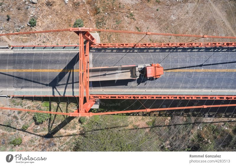 Truck crosses beautiful bridge in summer. Scene. Aerial view of truck carrying things driving across bridge on background expressway nature landscape mountains