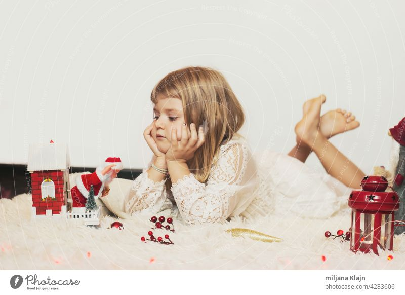 Little girl laying on the floor, playing with Christmas decoration; Christmas background with copy space box card carpet caucasian celebration child childhood