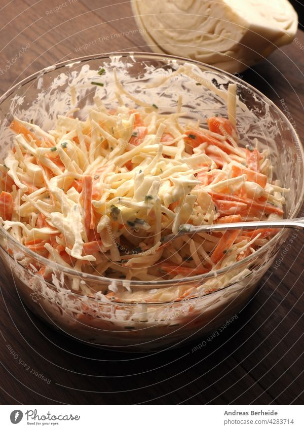 Traditional white cabbage salad with carrots ,chives, natural yogurt and vegan mayonnaise. Everything in organic quality appetizer bowl chopped closeup coleslaw