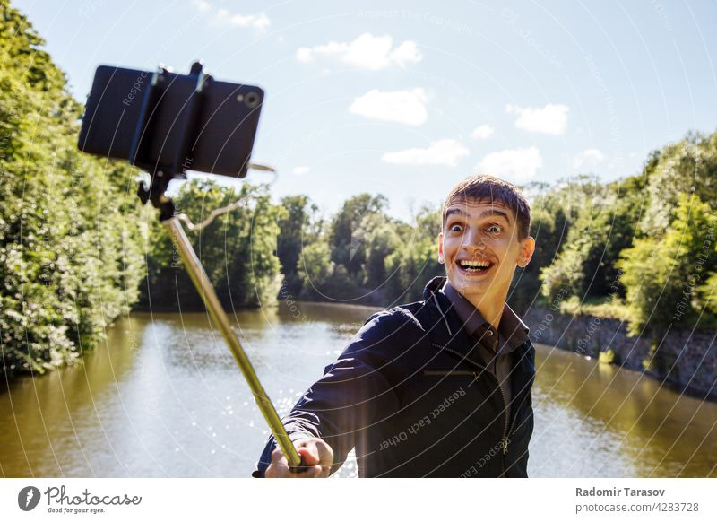 young man making selfie with a selfie stick male camera photo face portrait happy leisure background person make smartphone hand photographer mobile technology
