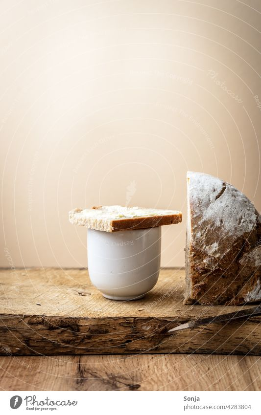 A slice of bread with butter on a coffee cup Coffee Bread Slice Butter Breakfast Wooden table Morning Food Nutrition Rustic Rural beige background Delicious