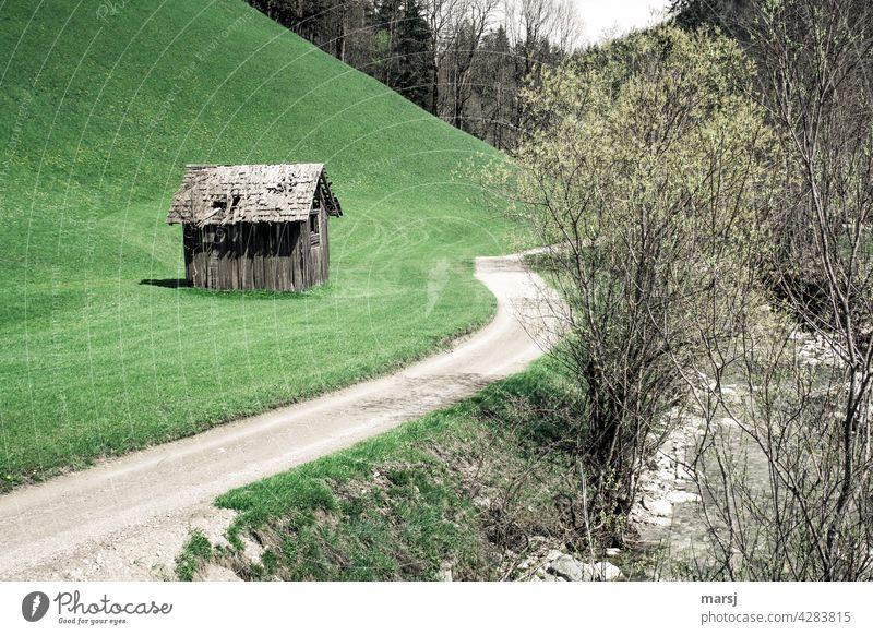 Cottage in the countryside, with its own driveway and stream. Lonely hay barn on a meadow next to a dirt road. Hut hay barnyard Colour photo Old Contrast Nature
