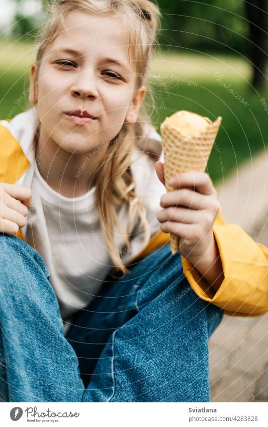 Portrait of a cute blonde teenage girl with ice cream on a walk in the park. Child outdoors summer teenager yellow funny trend happy child kid little dessert