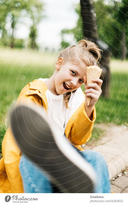 Portrait of a funny blonde teenage girl with ice cream on a walk in the park. Child outdoors summer teenager yellow trend happy cute child kid little dessert