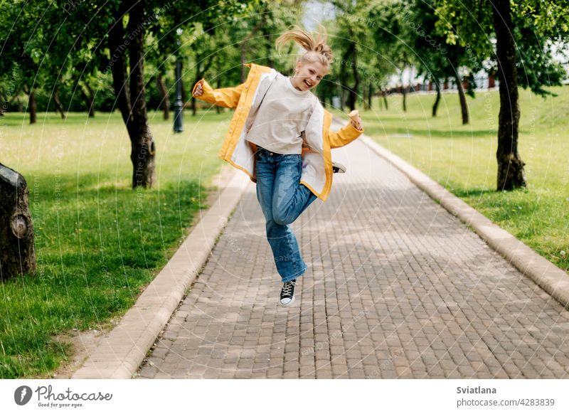 A teenage girl walking in the park jumping with ice cream in her hands. Child outdoors summer teenager back view funny trend blonde happy cute child kid little