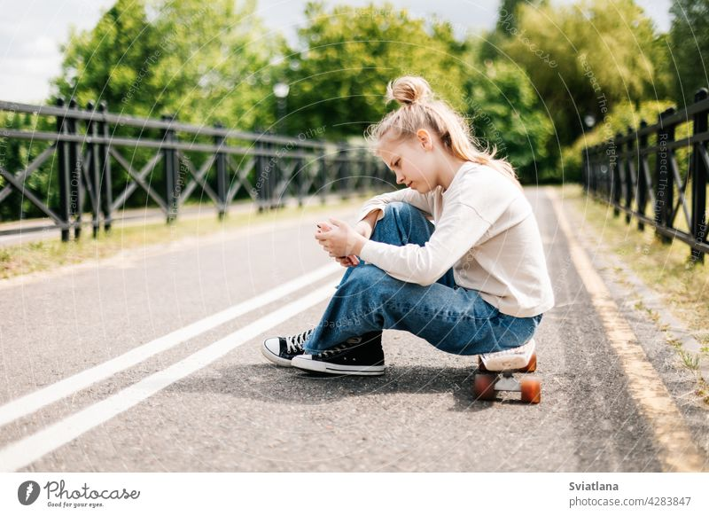 Cute blonde teenage girl sitting on a skateboard in a city park chatting on a smartphone with friends and taking a selfie. skating happy cheerful