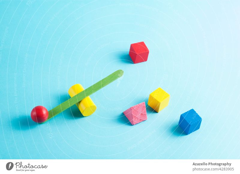 Minimal layout with a green and yellow swing scale and geometric figures on blue background balance minimalist composition 3d cube insight flexibility art