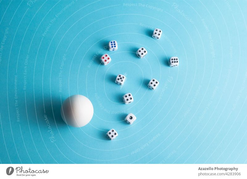 Minimal layout with a white egg and dice on blue background wager tabletop group concept minimalism life arm bet birth bone chance composition game goal hen