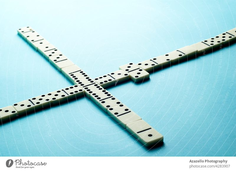 Domino pieces on blue background with an empty space for text copy minimalist symbolic domino bone gambling ivory stone game play think score champion leisure