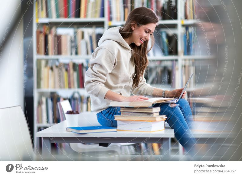 Young female student studying in the library enjoying lifestyle young adult people one person casual caucasian positive happy smiling woman attractive beautiful