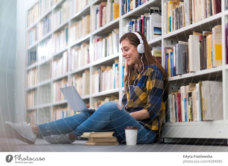 Female college student sitting in a library using a laptop enjoying lifestyle young adult people one person casual caucasian positive happy smiling woman female