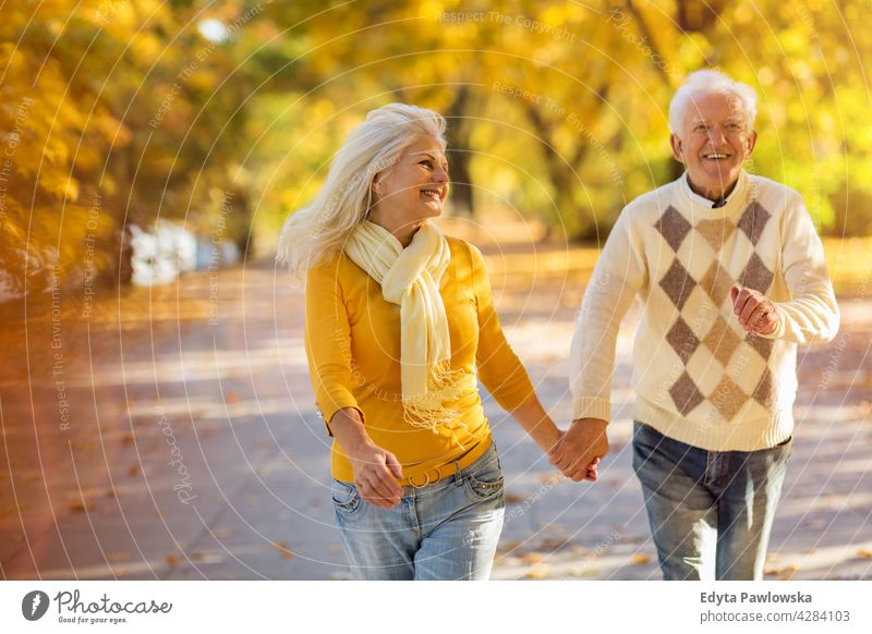 Mature couple running in autumn park family woman love people outdoors portrait together nature two beautiful fall trees yellow senior mature seniors pensioner