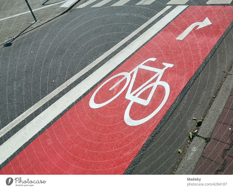 Newly built red bike lane with arrow for right turners on grey asphalt with zebra crossing in the West End of Frankfurt am Main in Hesse, Germany cycle path