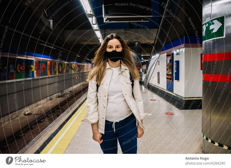 Young blonde woman with a face mask waiting for the subway in Madrid city. metro madrid spain masked virus train mobile phone disease station medical